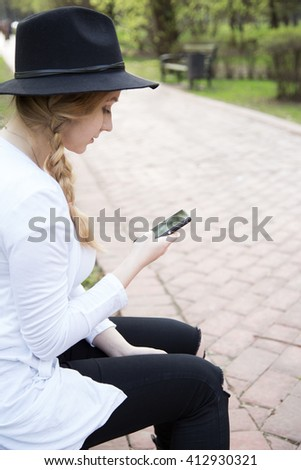 Style woman in hat sitting on bench texting using mobile phone, outdoors in park, summertime - stock photo
