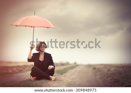 Style young women with umbrella at countryside outdoor. Photo in old color image style. - stock photo