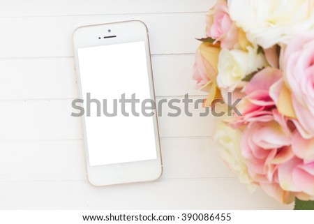 styled white wooden desktop  with modern phone  and flowers - stock photo