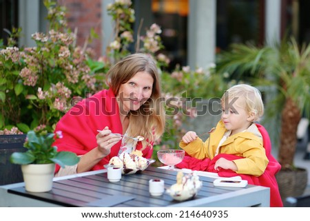 Styling caucasian family, happy mother, young beautiful woman and her little daughter, cute toddler girl, enjoying delicious dessert sitting outdoors in cozy city cafe on sunny autumn day - stock photo