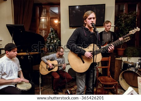 stylish acoustic band of young men playing and singing on a stage - stock photo