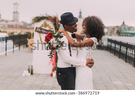Stylish african groom in hat and his pretty bride happily laughing. Wedding day - stock photo