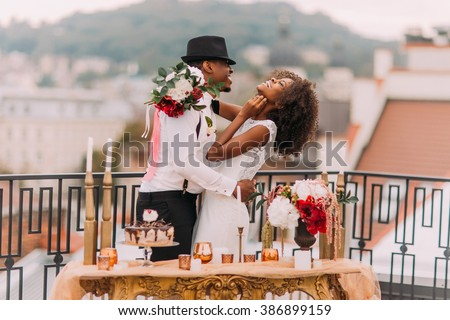 Stylish african wedding couple having fun on the balcony with luxury golden table in oriental style on foreground - stock photo