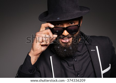 Stylish afro american man looking at camera over black background