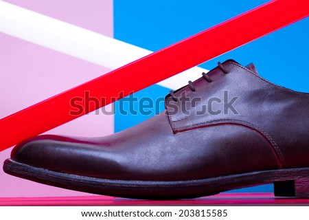 Stylish and arty hipster footwear fashion concept in disco style. Trendy leather men's shoes with red and white neon light lamps over pink, blue, purple background. Close up. Studio shot - stock photo