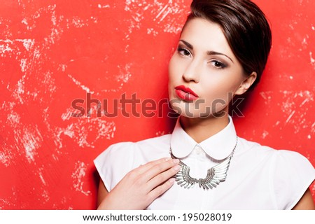 Stylish and beautiful. Beautiful young short hair woman in white shirt posing against red background  - stock photo