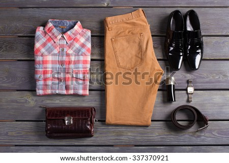 Stylish and colorful men's clothes lying on the wooden background. - stock photo