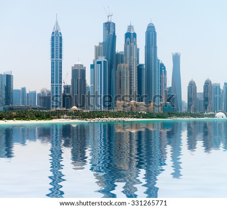 Stylish and contemporary architecture of a modern, metropolitan skyline, towering over a tropical beach and reflecting in a calm sea. - stock photo