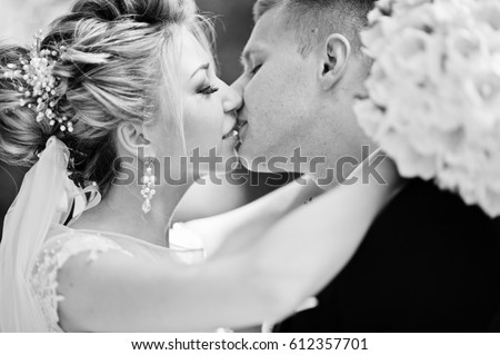Stylish and gorgeous kissing wedding couple walking outdoor at park on sunny weather.