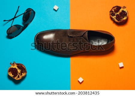Stylish arty hipster fashion concept in avant-garde style. Trendy eyewear and leather footwear on blue and orange background with pomegranates, sugar cubes. Copy-space. Studio shot - stock photo