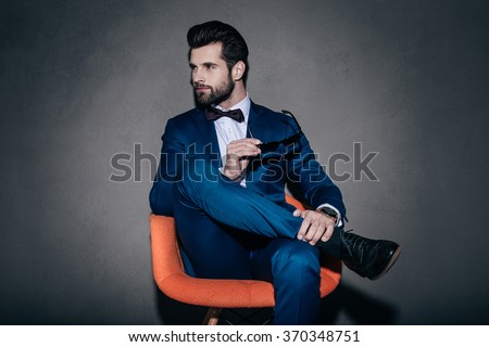 Stylish as ever. Young handsome man in suit holding his sunglasses and looking away while sitting in orange chair against grey background - stock photo