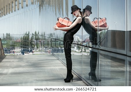 Stylish asian girl in a black suit and hat, posing with a glass wall - stock photo