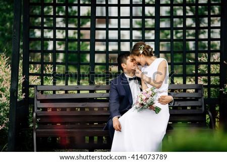 Stylish attractive happy bride and handsome groom lovely hugging on bench outdoors and looking away. Copyspace at the left. Beauty bride with groom. Cute lady and handsome guy - stock photo