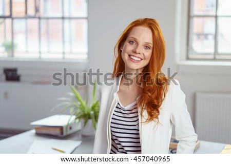 Stylish attractive young redhead businesswoman with a lovely smile standing in front of a table in the office grinning at the camera