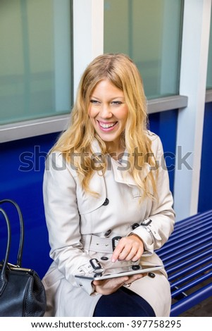 Stylish attractive young woman sitting waiting for transport on a bench outdoors drinking coffee and reading information on her tablet computer