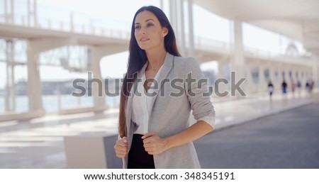 Stylish attractive young woman with long hair standing outdoors on an urban promenade  architectural elements with copyspace