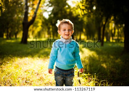 stylish baby boy having fun outside in the park,laughing