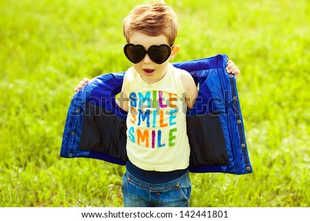 Stylish baby boy with ginger hair in trendy sunglasses (heart form) & blue jacket standing in the park and singing a song. Hipster style. Sunny weather. SMILE word printed o t-shirt. Outdoor shot - stock photo