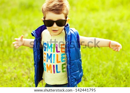 Stylish baby boy with ginger (red) hair in trendy sunglasses and blue jacket standing in the park & trying to hug somebody. Hipster style. Sunny weather. SMILE word printed on t-shirt. Outdoor shot - stock photo
