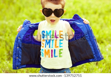 Stylish baby boy with ginger (red) hair in trendy sunglasses (heart form) and blue jacket standing in the park and singing a song. Hipster style. Sunny weather. Outdoor shot - stock photo