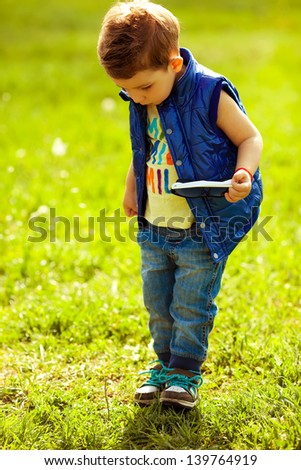 Stylish baby boy with ginger (red) hair with trendy sunglasses in his hand standing in the park and looking for something in the grass. Hipster style. Sunny weather. Outdoor shot - stock photo