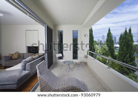 Stylish balcony with chais lounge and chairs overlooking the city - stock photo