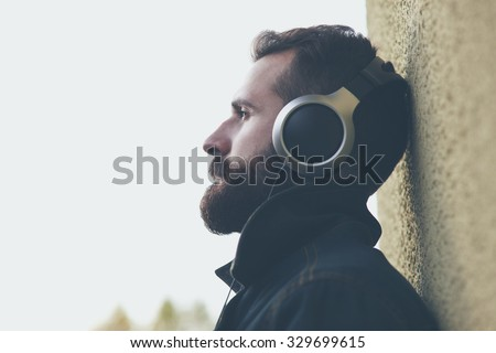 stylish bearded man  in headphones listening to music - stock photo