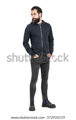 Stylish bearded punker wearing worn old leather boots looking down. Full body length portrait isolated over white studio background.