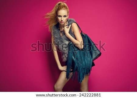 Stylish beautiful blonde woman wearing feather vest holding nice big fringed handbag. Fashion picture - stock photo