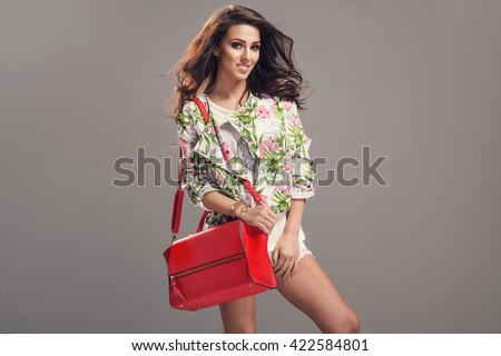 Stylish beautiful brunette woman wearing flower pattern jacket, white shorts holding nice handbag. Fashion picture. Creative hair style. - stock photo