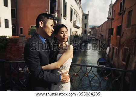 Stylish beautiful couple Asians newlyweds walking on the Venice streets on a sunny day of their wedding