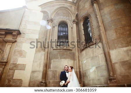Stylish beautiful couple on the background of old stone church