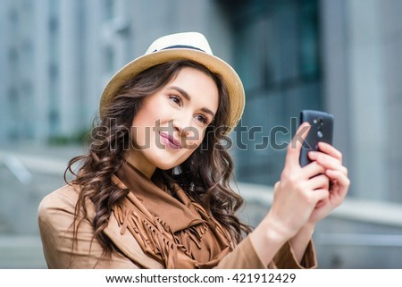 Stylish beautiful girl dressed in boho style with a smartphone on the background of the business center. Smiling woman doing selfie. Vacation  Europe.