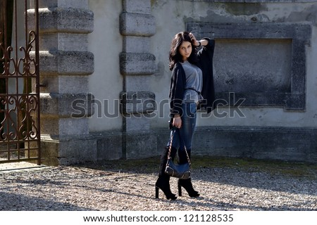 Stylish beautiful girl is posing in the courtyard  of the old castle  under bright sunbeams. Tuscan, Italy - stock photo
