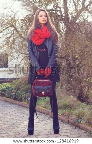 stylish beautiful girl posing outdoors in black leather jacket, red scarf and red gloves - stock photo