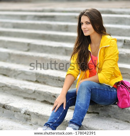 Stylish beautiful girl sitting on a stairs in colorful clothes  - stock photo