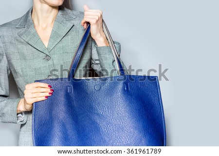 Stylish beautiful woman with bag on grey background