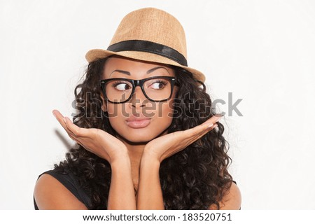 Stylish beauty. Portrait of beautiful young African woman in glasses and funky hat gesturing and looking away while standing against white background - stock photo