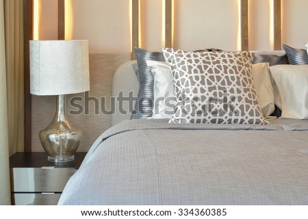 stylish bedroom interior design with brown pillows on bed and decorative table lamp. - stock photo