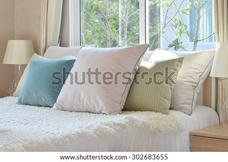 stylish bedroom interior design with colorful pillows on bed and decorative table lamp. - stock photo