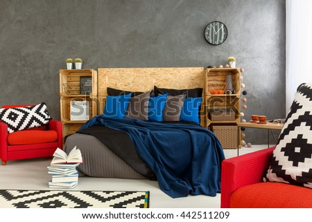 Stylish bedroom with grey walls and red armchair with little mess on bed. Wooden headboard of the bed and shelves made of wooden boxes