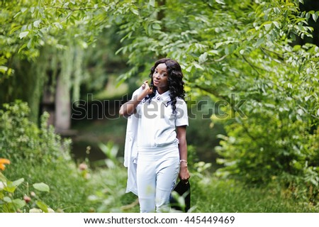 Stylish black african american girl holding jacket on her shoulder at green park - stock photo