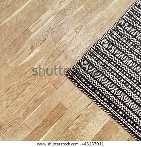 Stylish black and white rug with ethnic design on hardwood floor.