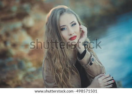 Stylish blond girl in a coat on a sea cliff. portrait of a girl with red lipstick