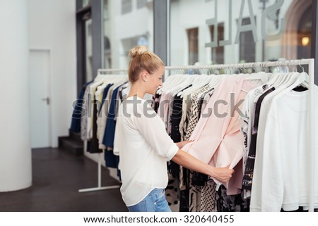 Stylish Blond Girl Looking at the Clothes Hanging on Rail inside the Clothing Store - stock photo
