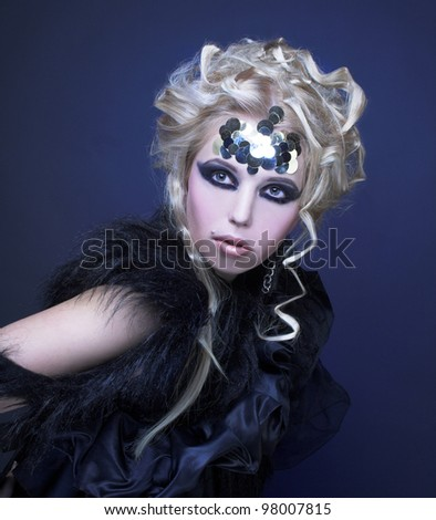 Stylish blond woman in dark dress with furs and with artistic visage