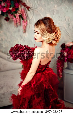stylish blonde beautiful woman in red cloud dress with curly hairstyle. Flowers.