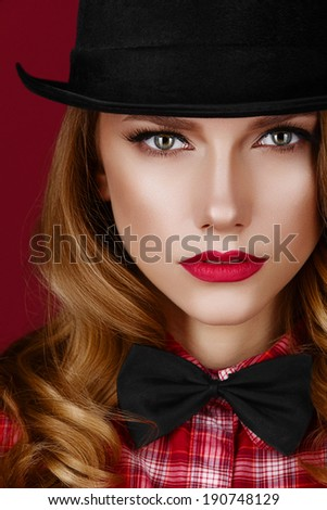 Stylish blonde girl in a black vintage hat and bow tie with bright red lips. - stock photo