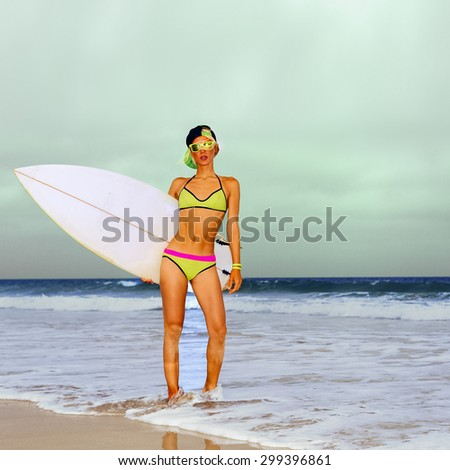 Stylish Blonde standing on the beach with Surf board. - stock photo