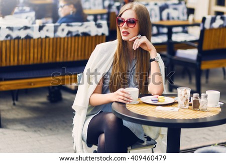 Stylish blonde  woman sitting in cafe on terrace drinking coffee  with macaroons, dreaming, enjoying weekend. Soft vintage toned colors. Wearing stylish sunglasses, fall outfit. - stock photo
